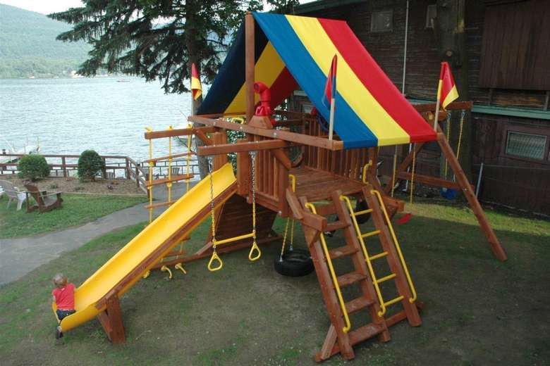 playground with a yellow slide and a blue, yellow, and red tent