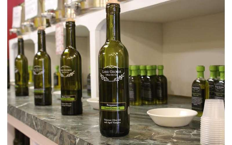 Bottles of Lake George Olive Oil on a marble slab.
