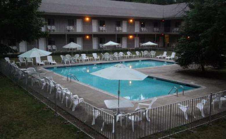 L-shaped outdoor pool, lots of white chairs and umbrellas