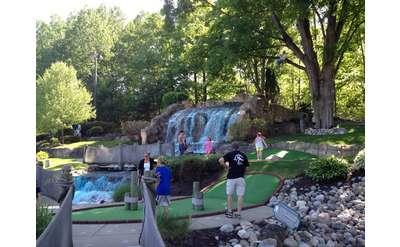 waterfall with people playing mini golf