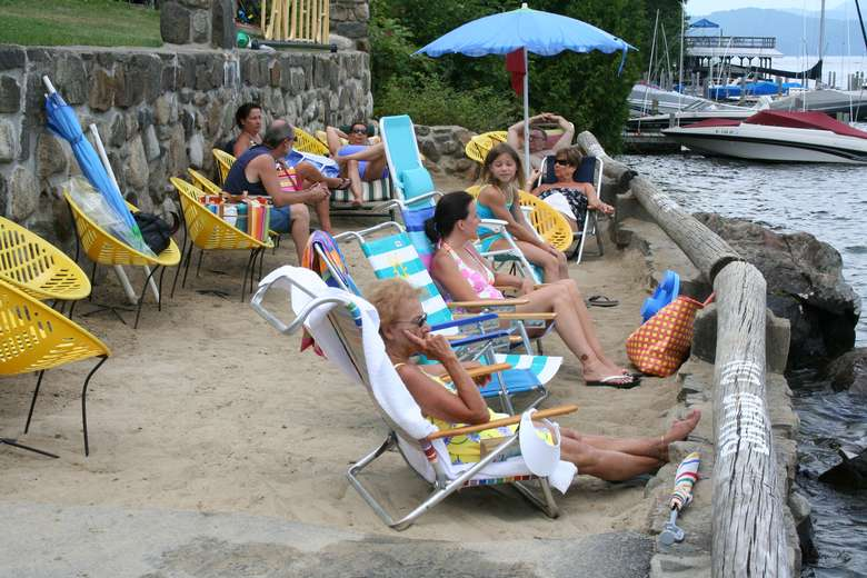 people relaxing in beach chairs by the water