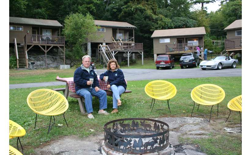 a couple sitting in chairs around a spot for a bonfire