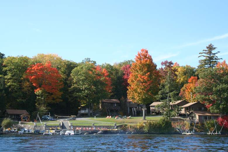 view of cottages from the water, fall foliage on trees