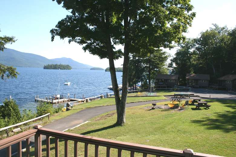 view from cottage of lawn, trees, picnic tables, lake, docks