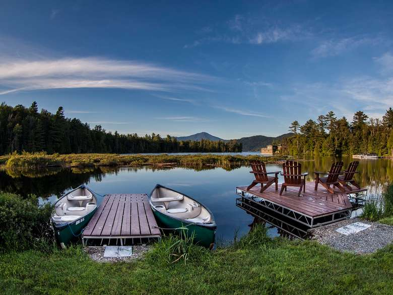 Docks with canoes and Adirondack chairs