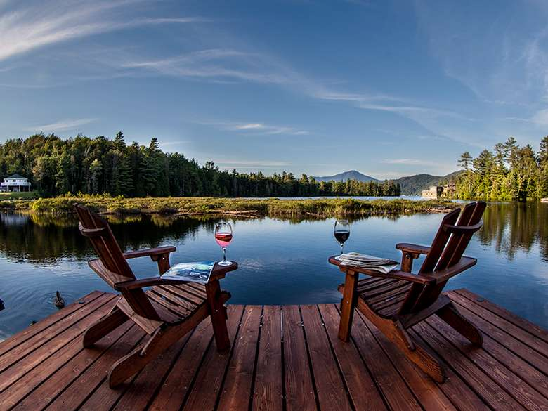 Two Adirondack chairs with wine glasses by the lake