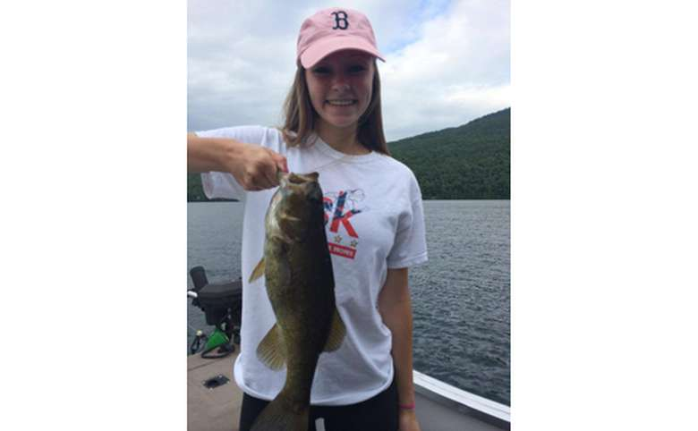 Girl in a pink baseball hat holding a bass