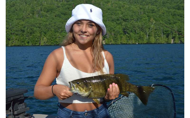 A girl in a white hat holding a bass
