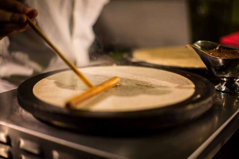 chef using a wooden tool to spread batter into a crepe