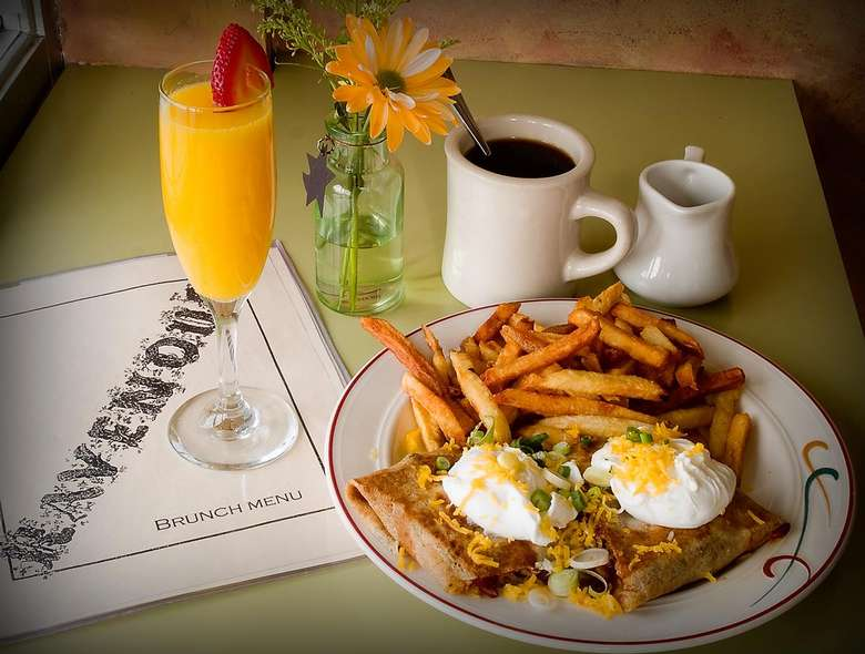 crepes with poached eggs on top, a side of fries, coffee, and a mimosa