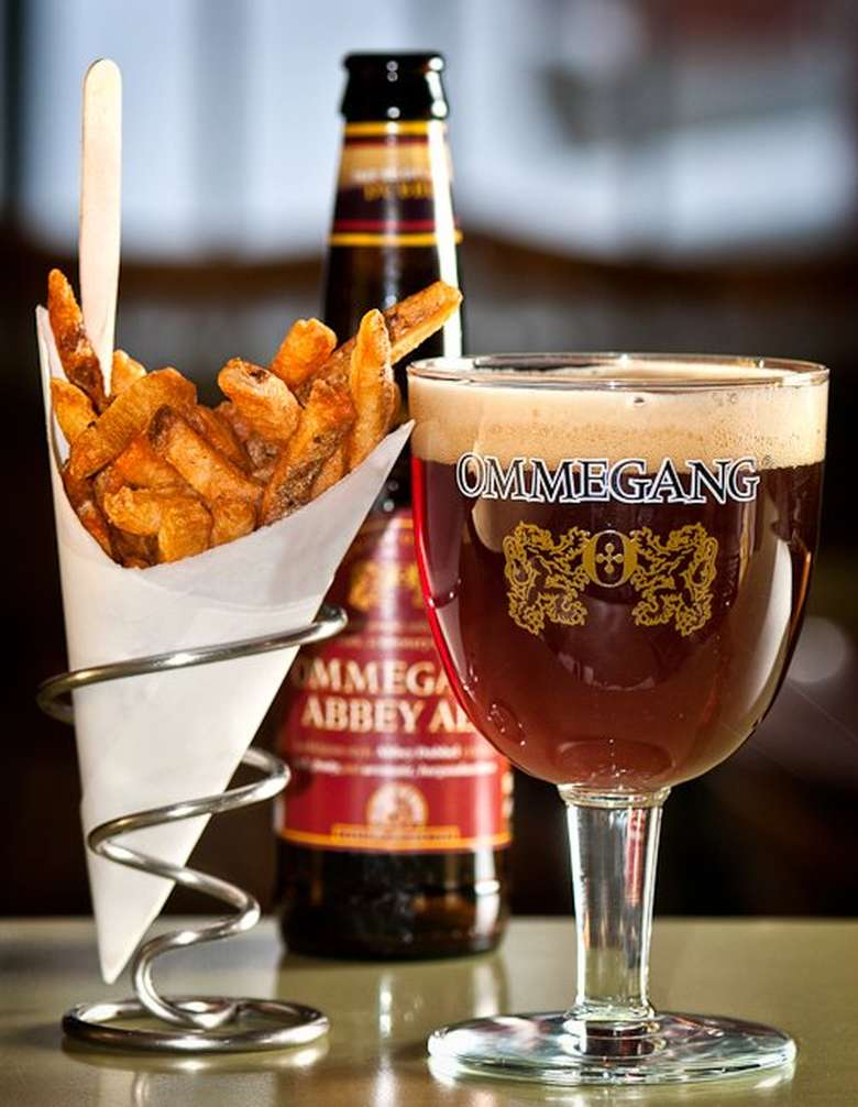basket of fries next to a bottle and glass of beer
