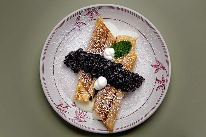 two crepes on a plate with a blueberry topping