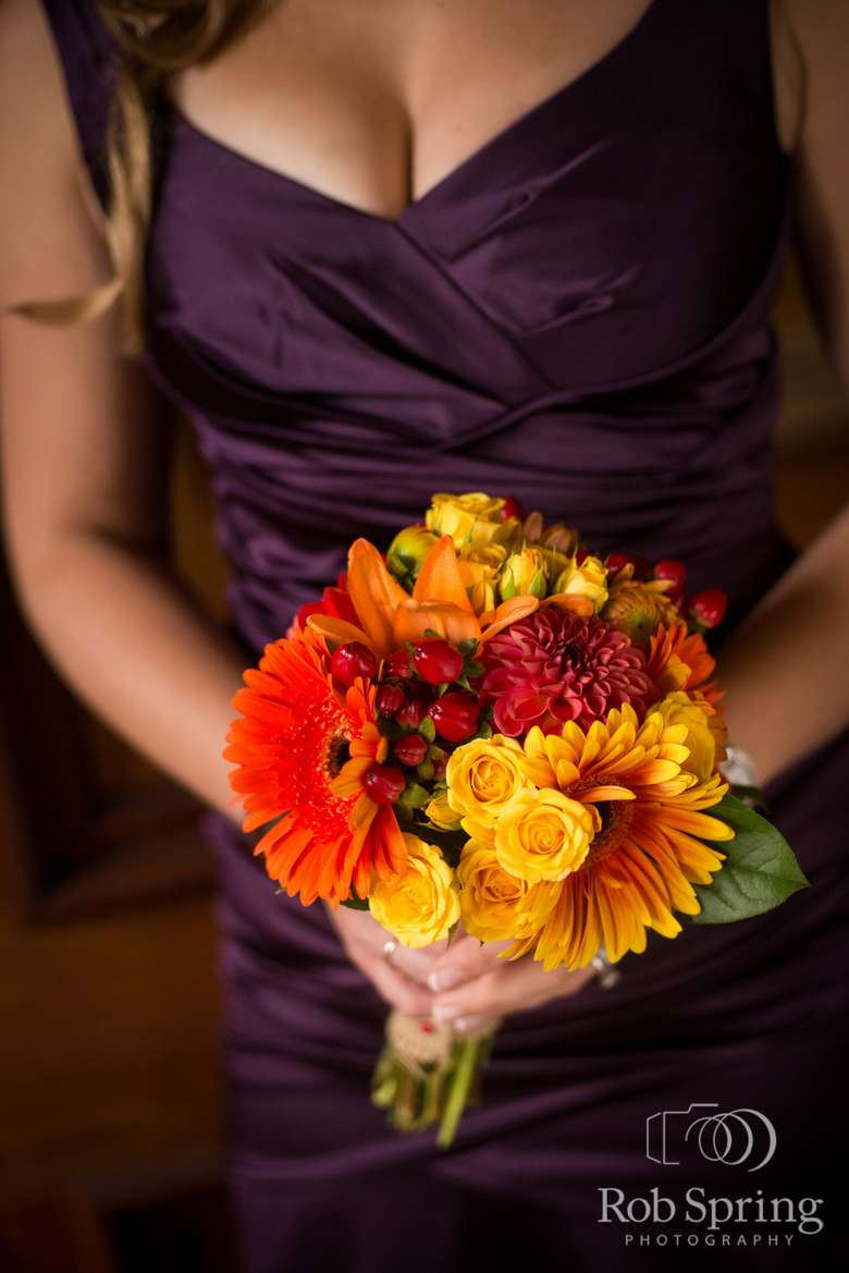 Woman in a bridesmaid dress holding a bright bouquet
