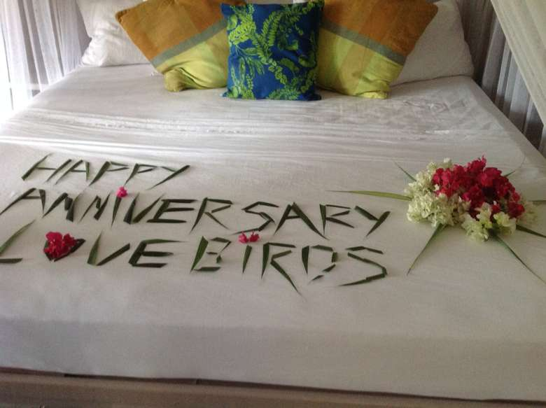 Happy anniversary love birds written in leaves on bed
