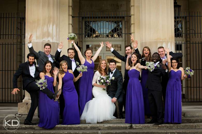 Wedding party with their arms in the air looking excited
