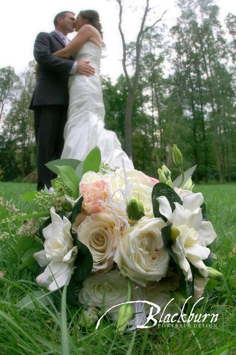 floral bouquet on the ground with couple kissing behind it