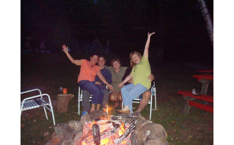 five people waving at the camera in front of a campfire