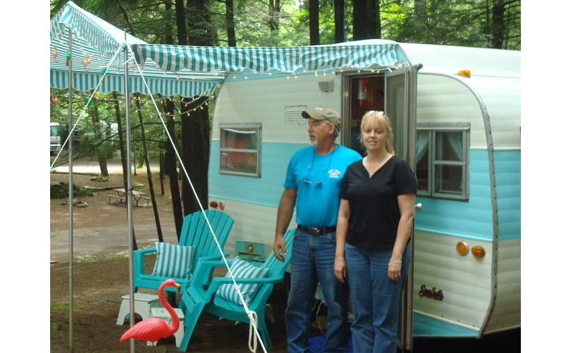 a man and woman standing outside the entrance of a small camper