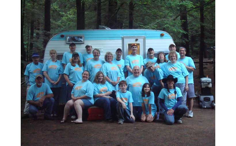 large group of people wearing the same colored shirt in front of a small blue and white camper
