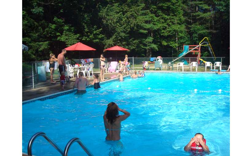 a full view of a bright blue outdoor pool with just a few people in the shallow section
