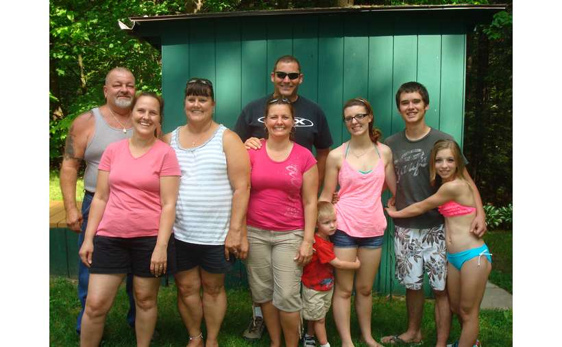 nine people standing in front of a green shed for a group photo