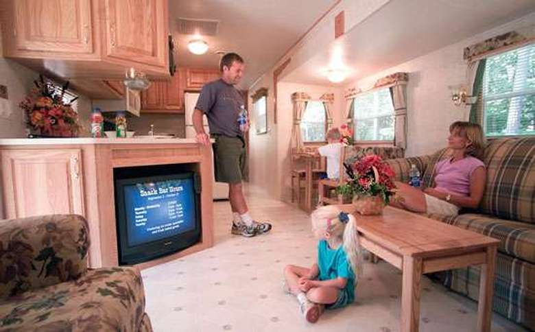 family inside spacious camper watching TV