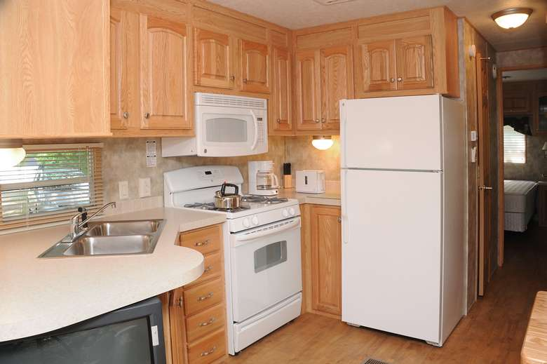kitchen with white fridge, cabinets, oven, stove, sink