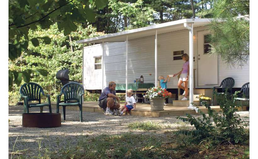 a family hanging out on a porch in front of a trailer