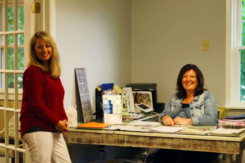 one woman sitting at a desk while another woman stands near it
