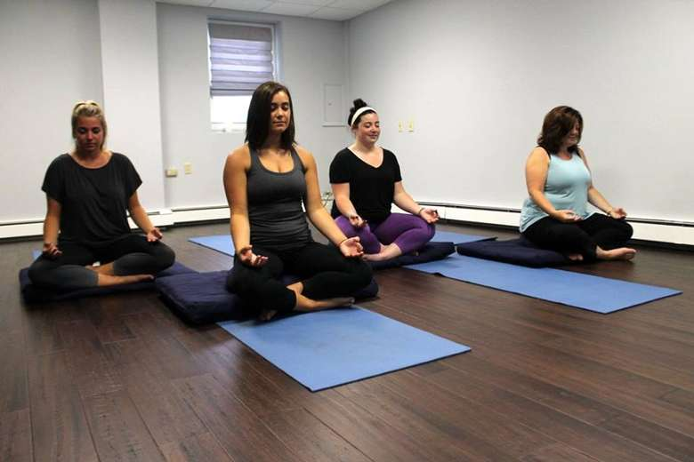 four women sitting for a yoga session