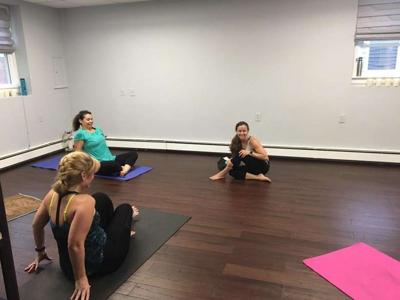 two women on yoga mats, and one woman sitting on the floor