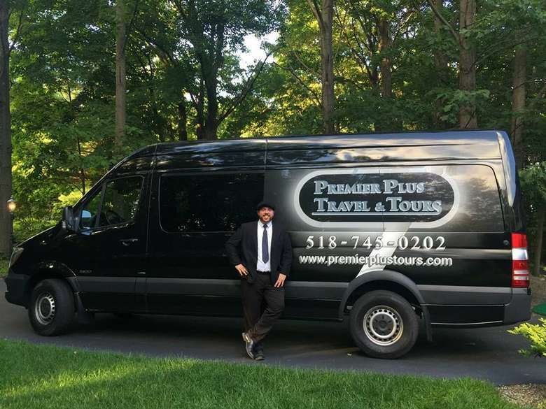 driver in a suit standing in front of a premier plus travel and tours van
