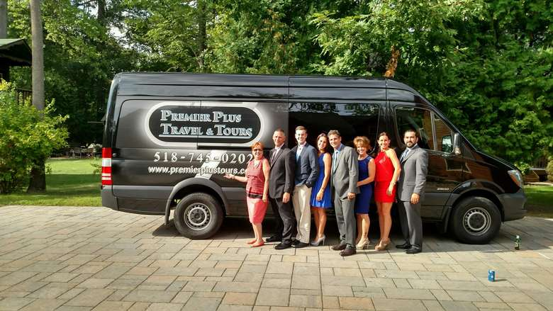 eight people standing in front of a premier plus travel and tours van