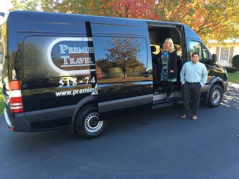 two people climbing out of a premier plus travel and tours van