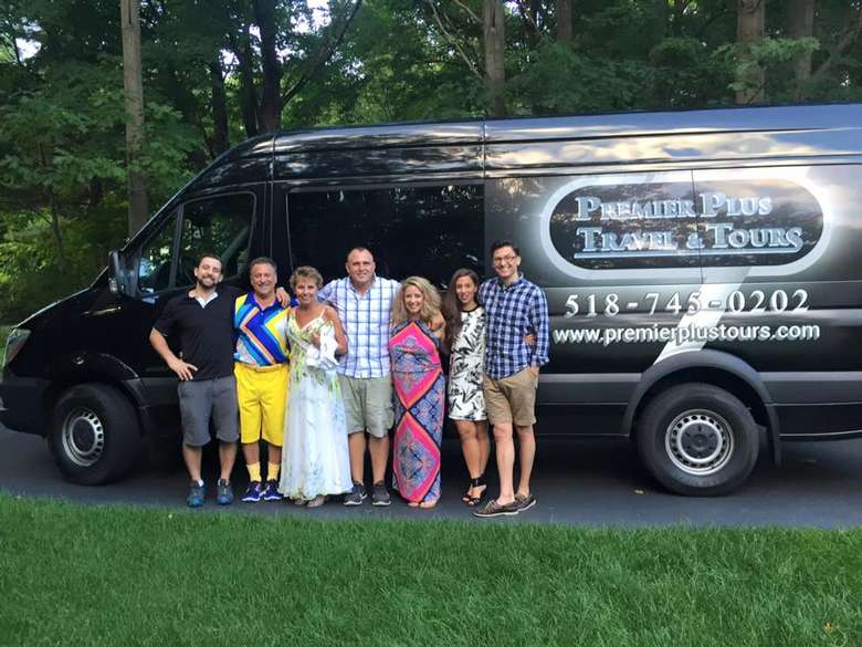 seven people standing in front of a premier plus travel and tours van