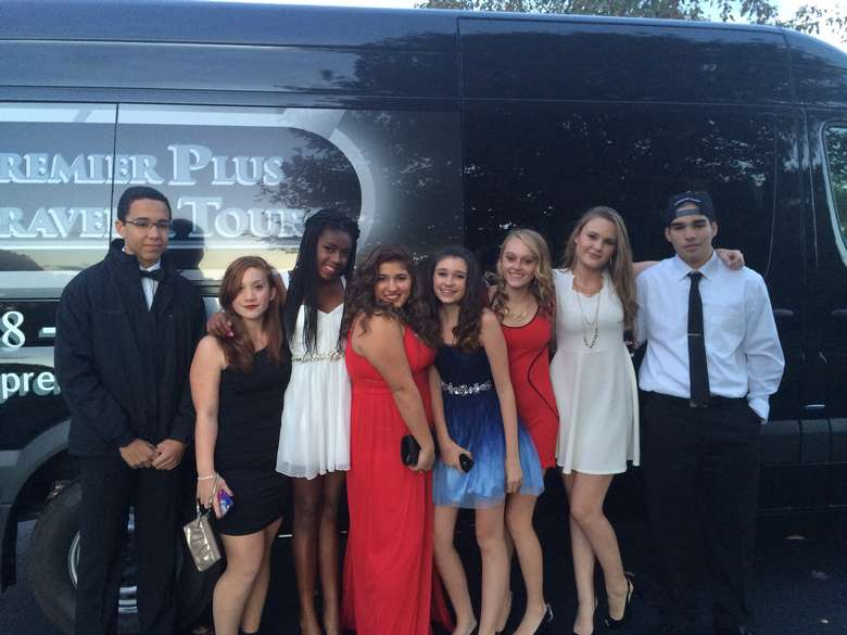 eight teens dressed up for a semi-formal dance standing in front of a premier plus travel and tours van