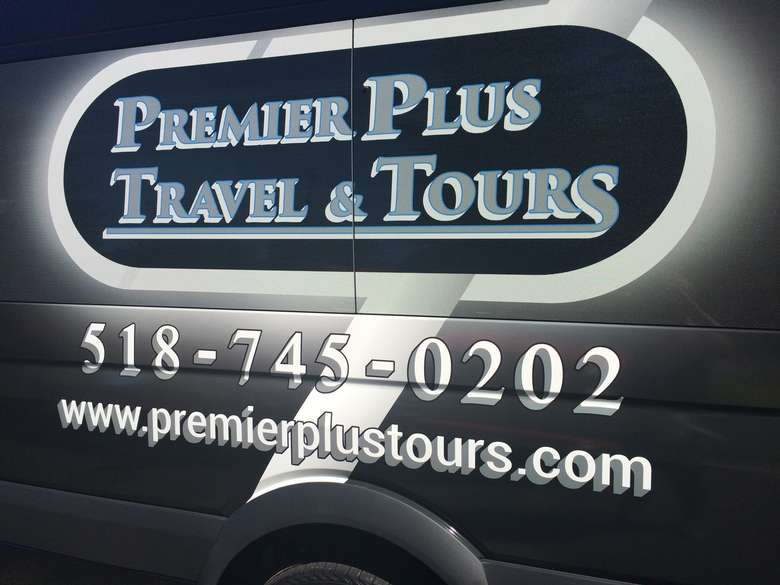 premier plus travel and tours logo on the side of a black van