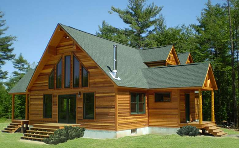 wooden home with a green roof and log columns