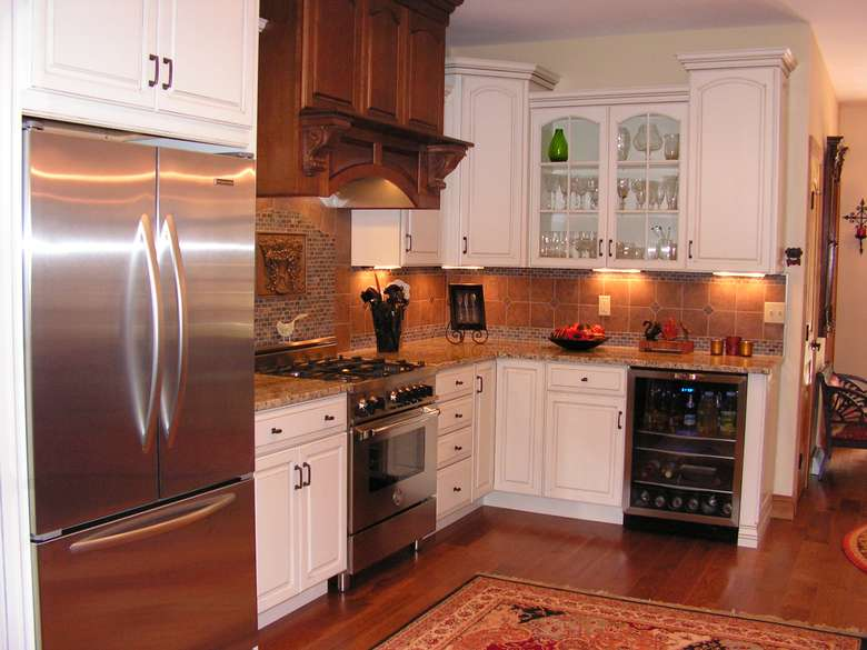 remodeled kitchen with white cabinets, stainless appliances, and a tiled backsplash