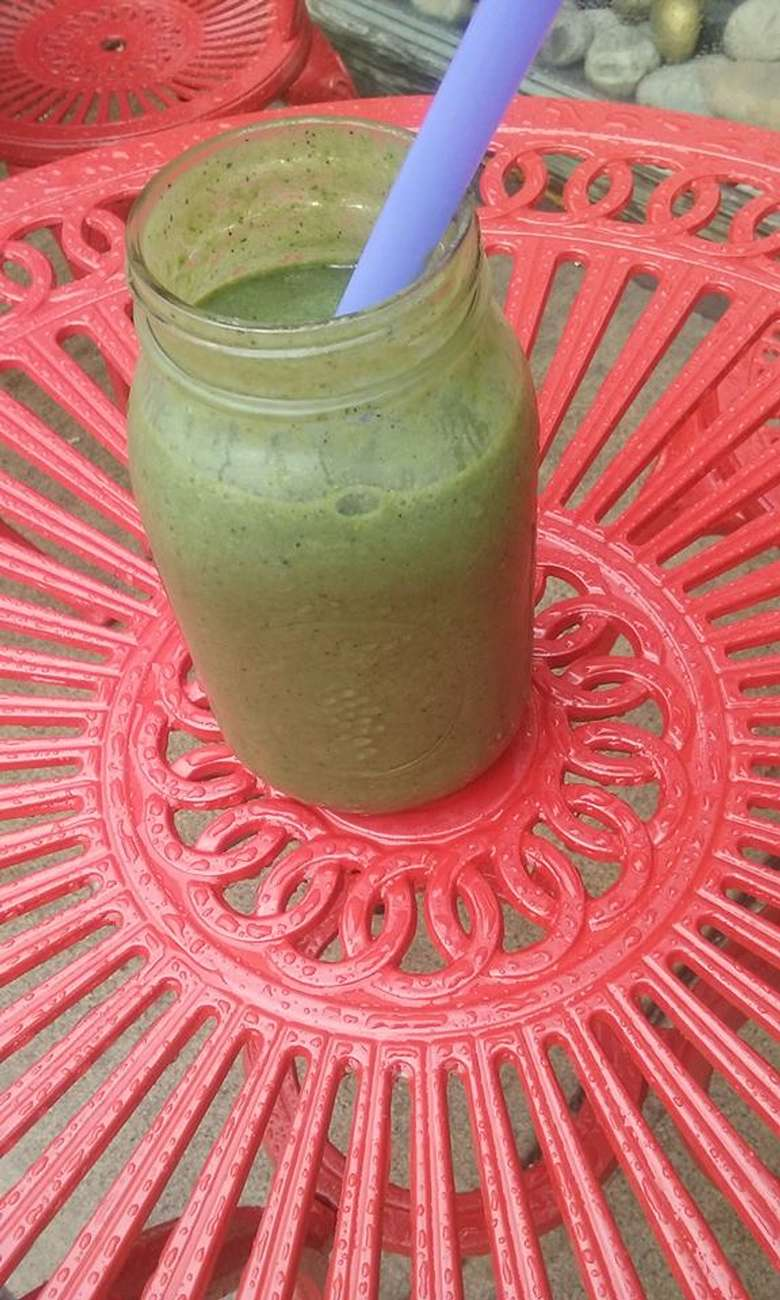 green smoothie in a mason jar with a purple straw on a pink table
