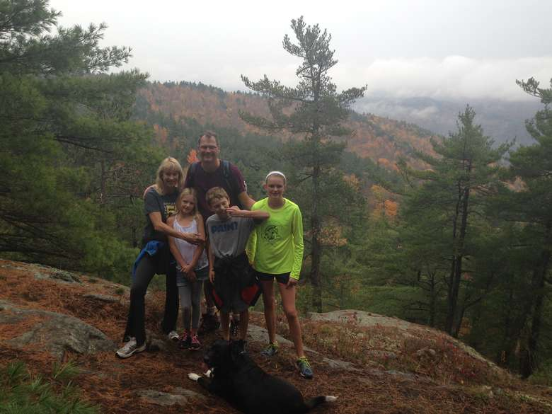 family posing for a picture while hiking in the fall