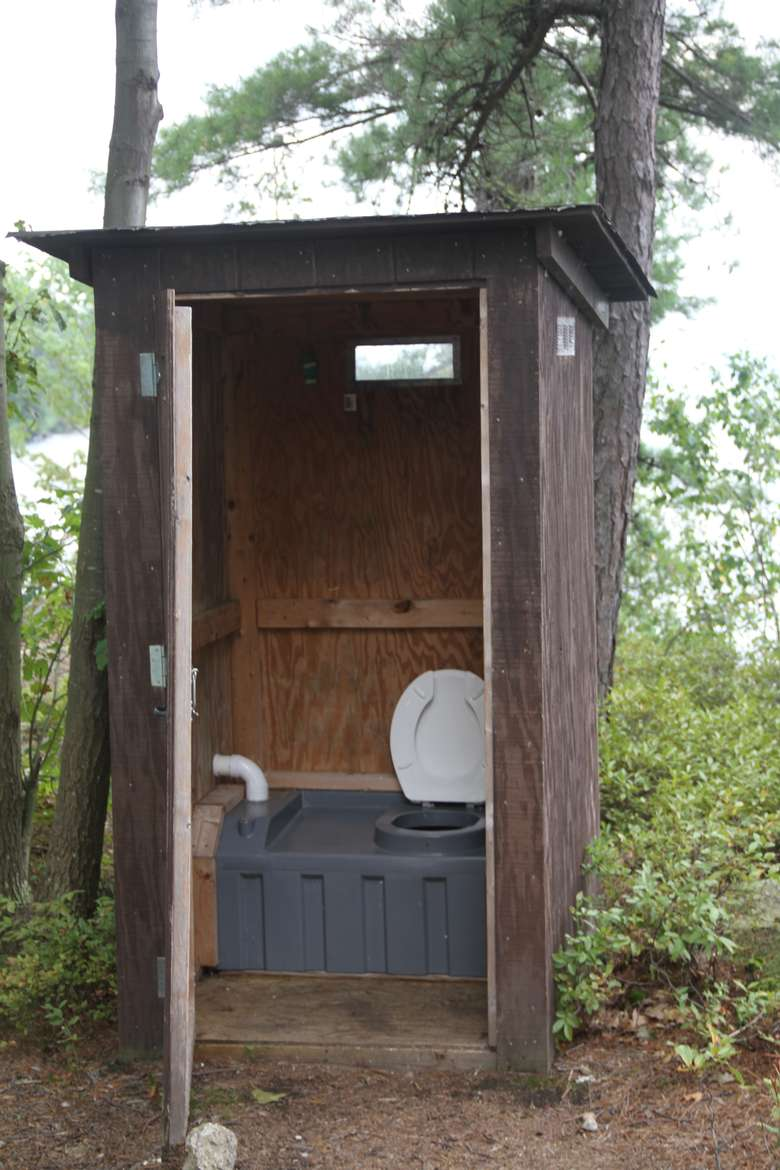 an open wooden outhouse in the woods