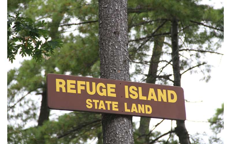 the sign for refuge island state land attached to a tree