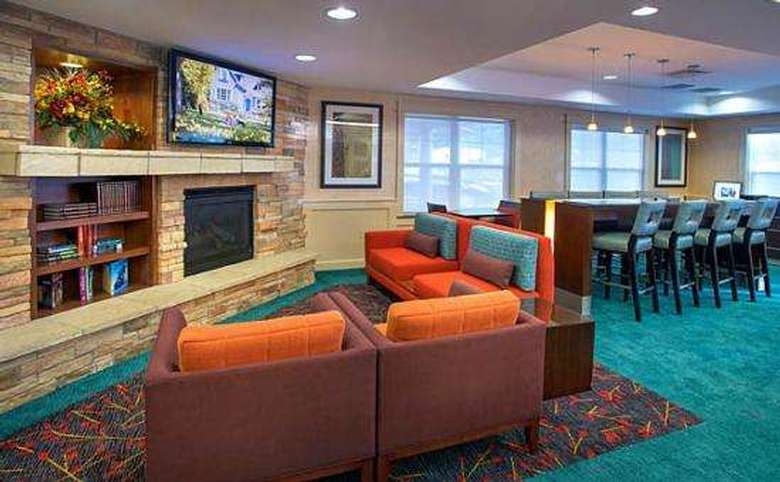 couches and chairs in front of a fireplace and tv in a hotel lobby