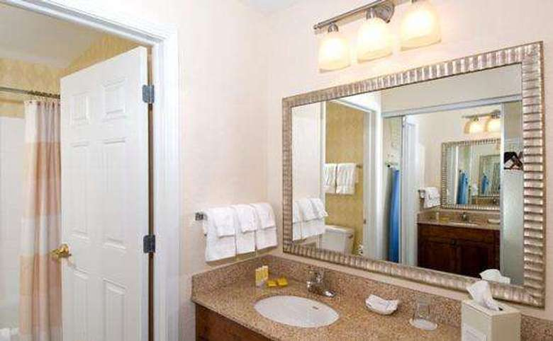 sink, vanity, and mirror next to a door that leads into a separate room with a shower and toilet