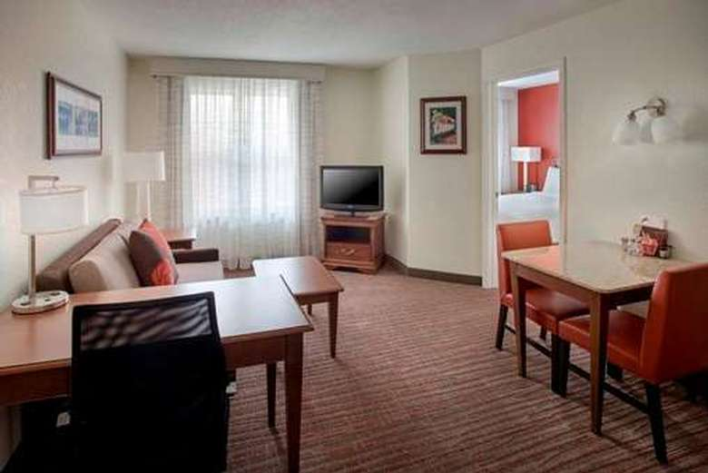 one bedroom suite with a bedroom in one room and a seating area in the other