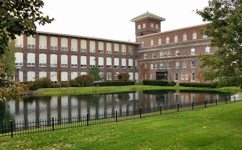 Exterior of a large brick building with a pond in front of it