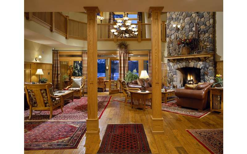 the downstairs of the lodge with wooden pillars, stone fireplace, furniture