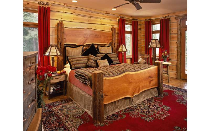 a bedroom decorated in wood panels with a wooden bed and dresser, red curtains