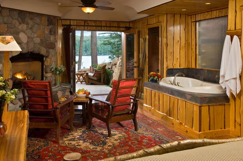 a hot tub in a living room with as tone fire place, view of a patio outside